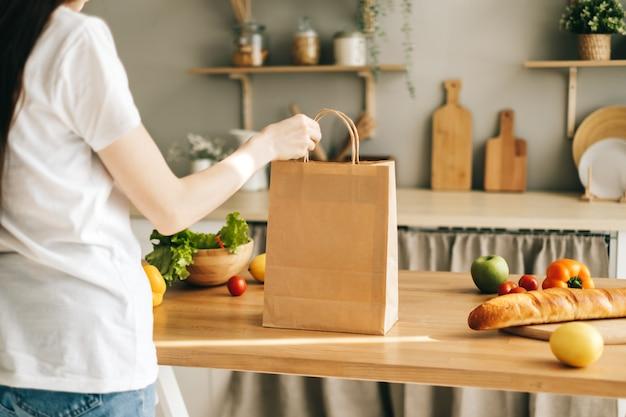 Blanke vrouw houdt eco boodschappentas met verse groenten in de keuken