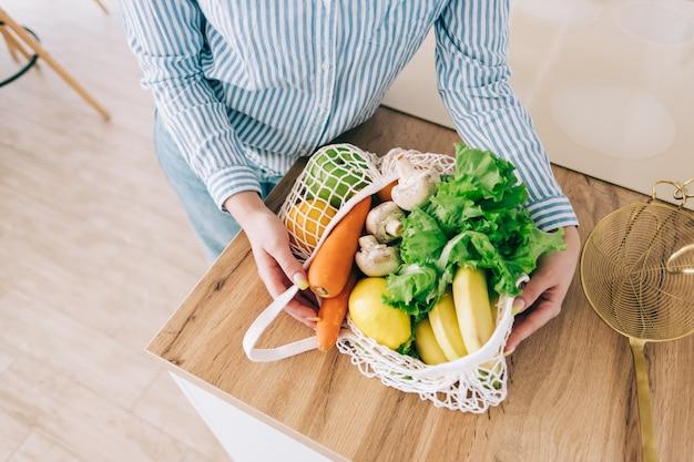Blanke vrouw houdt eco netzak met verse groenten in de moderne keuken.