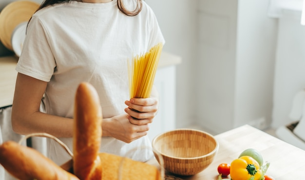 Blanke vrouw houdt tarwe spaghetti pasta in handen