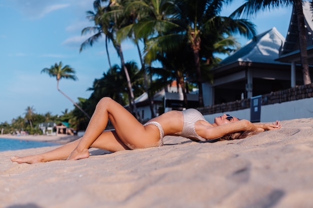 Blanke vrouw in bikini en zonnebril op tropisch strand