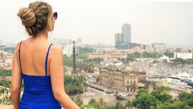 Blanke vrouw in blauwe jurk met uitzicht op barcelona op de achtergrond, spanje