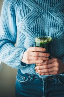 Blanke vrouw in een blauwe gebreide trui poseren met een glas vers groentesap