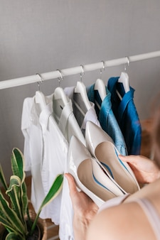 Blanke vrouw in haar huis met schoenen en in haar garderobe kleding kiezen voor werk of voor een wandeling en ontmoeting met vrienden
