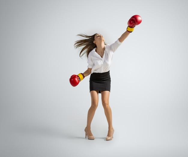 Blanke vrouw in kantoorkleding boksen op grijs