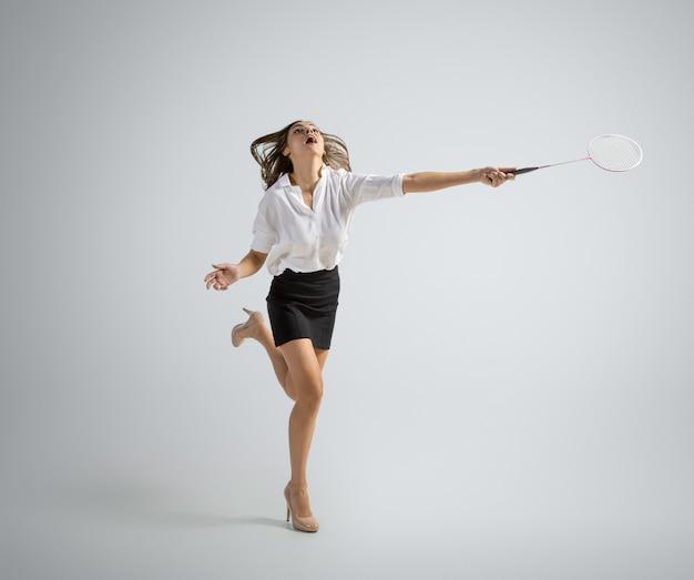 Blanke vrouw in kantoorkleding speelt badminton geïsoleerd op een grijze muur
