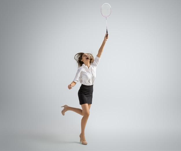 Blanke vrouw in kantoorkleren speelt badminton geïsoleerd op een grijze muur
