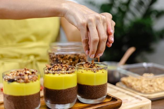 Blanke vrouw in keuken maakt chia puddingen met mangocam. woestijn gemaakt van amandelmelk, chiazaad, cacao, mangocam en granola.