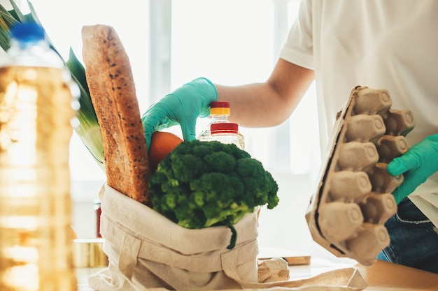 Blanke vrouw in keuken unboxing producten gekocht via online levering tijdens lockdown