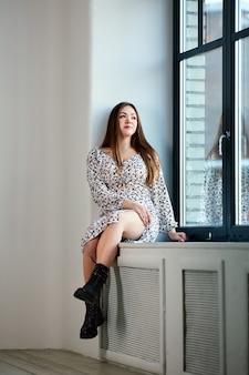 Blanke vrouw in laarzen in militaire stijl zit op de vensterbank