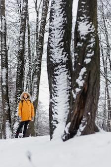 Blanke vrouw in oranje jas wandelen in een winterpark in het midden van de bomen in de natuur, genietend van de wandeling en het winterlandschap en de stilte