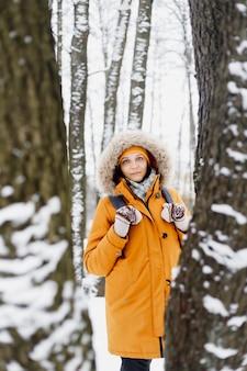 Blanke vrouw in oranje jas wandelen in een winterpark in het midden van de bomen, portret van een vrouw in de natuur, die geniet van een wandeling en het winterlandschap