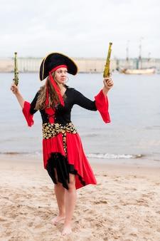 Blanke vrouw in piraat kostuum verhoogd naar de top twee speelgoed geweren.