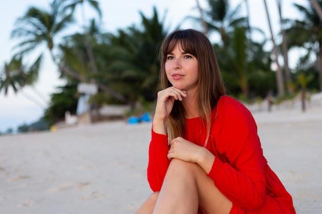 Blanke vrouw in rode zomerjurk in romantische gelukkige stemming op tropisch wit zandstrand bij zonsondergang