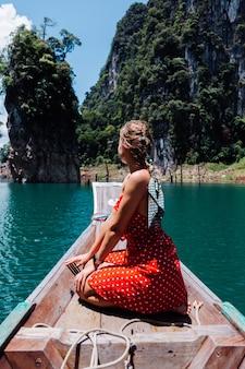 Blanke vrouw in rode zomerjurk op thaise aziatische boot op vakantie, reizen door thailand