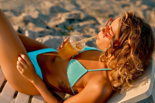 Blanke vrouw in zonnebril en een badpak drinkt sap of limonade en zonnebaadt terwijl ze op een ligstoel op het strand ligt.