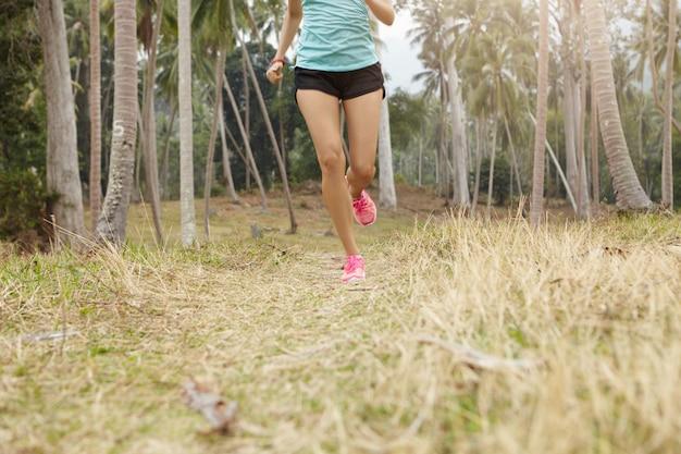 Blanke vrouw jogger met mooi fit lichaam draait op gras in tropisch woud. jonge vrouwelijke atleet die blauwe sporttop en zwarte broek draagt die buiten op zonnige dag uitoefent.