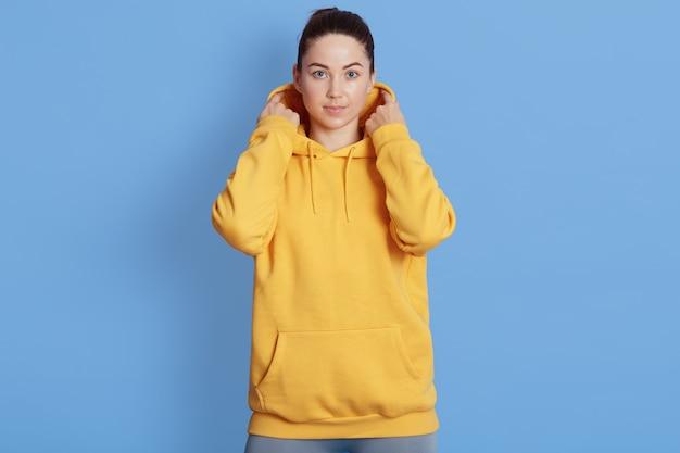 Blanke vrouw kijkt naar de camera, draagt een geel sweatshirt, poseren geïsoleerd op blauwe achtergrond, houdt de handen op de motorkap, heeft ernstige gezichtsuitdrukking.