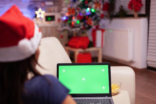 Blanke vrouw kijkt naar mock-up groen scherm chroma key laptop met geïsoleerd scherm