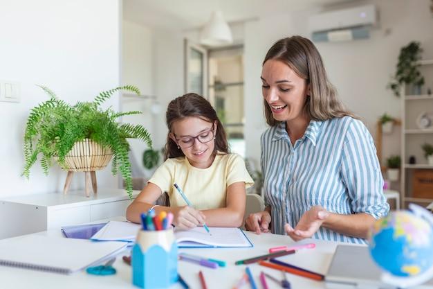 Blanke vrouw kijkt trots naar haar dochter tijdens thuisonderwijs en schildert.