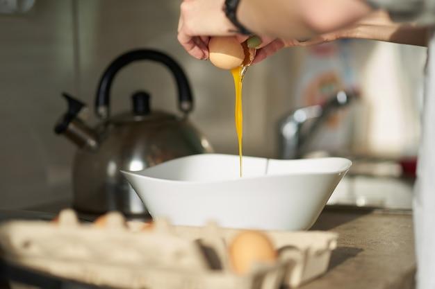 Blanke vrouw kraken open een ei tijdens het ontbijt koken. close-up handen