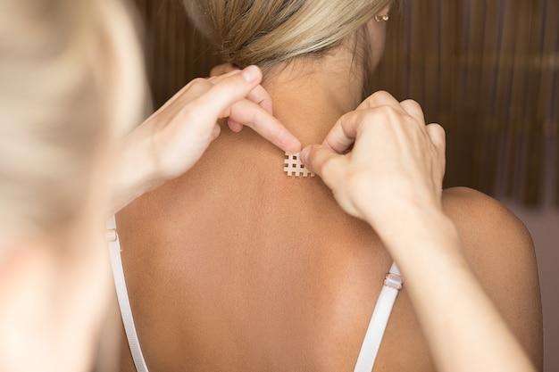 Blanke vrouw krijgt een kruis kinesiotape in haar nek voor pijnverlichting bij cervicaal syndroom
