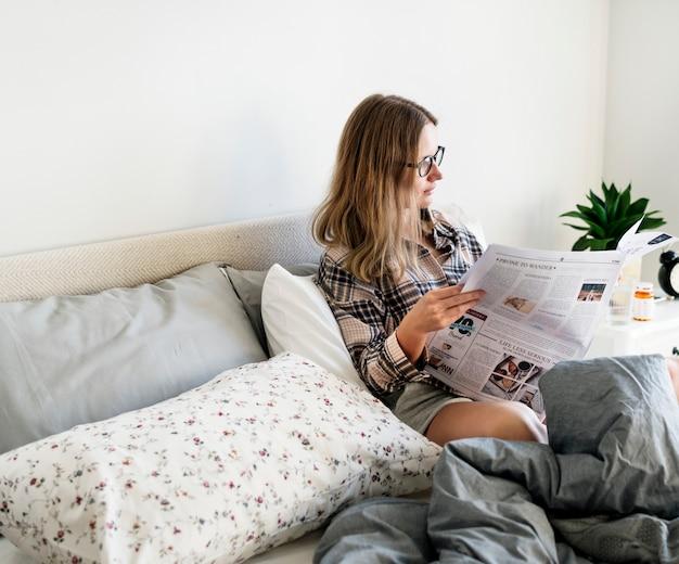 Blanke vrouw leest de krant op bed