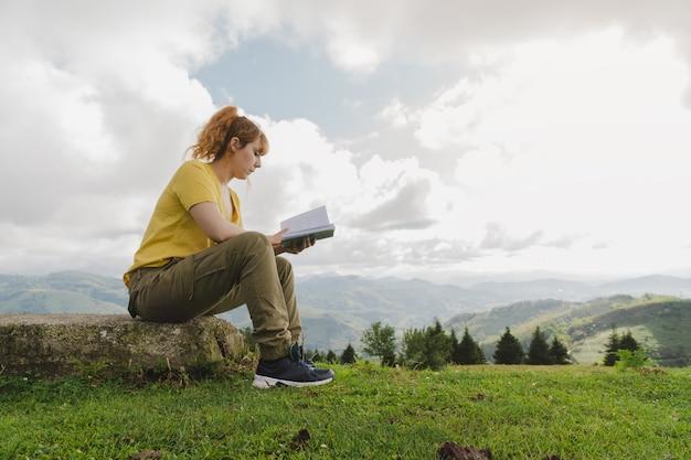 Blanke vrouw leest een boek in een bos midden in de natuur met bergen op de achtergrond