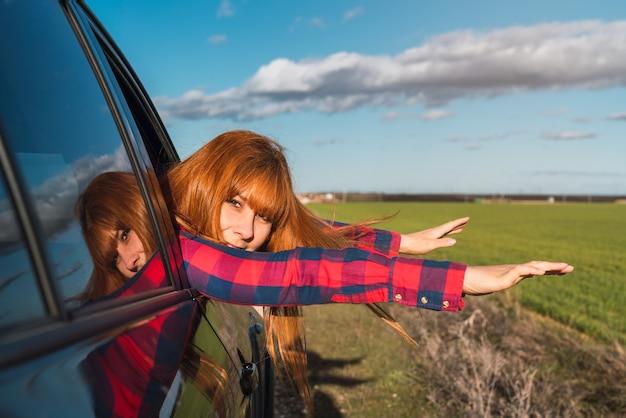 Blanke vrouw leunend uit een autoraam met uitgestrekte armen in het veld vrijheidsconcept