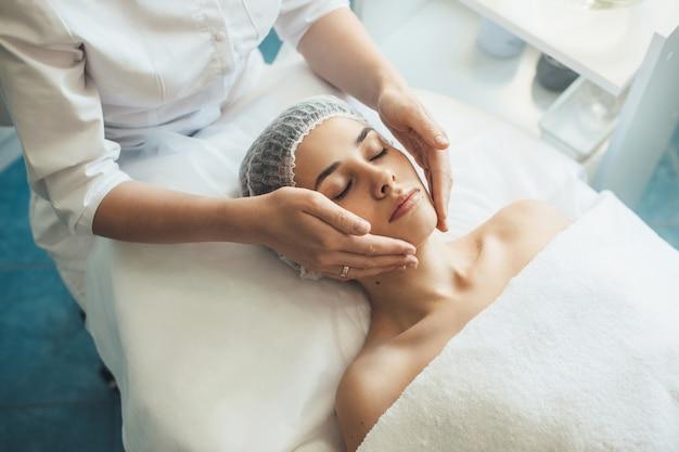 Blanke vrouw liggend op een bank in spa salon met een gezichtsmassage
