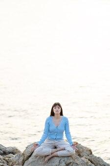 Blanke vrouw mediteert voor de zee in vrijetijdskleding
