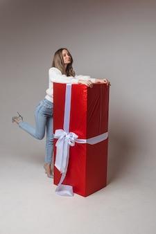 Blanke vrouw met aantrekkelijk uiterlijk verheugt zich over een groot cadeau voor st. valentijnsdag, foto geïsoleerd op een witte achtergrond