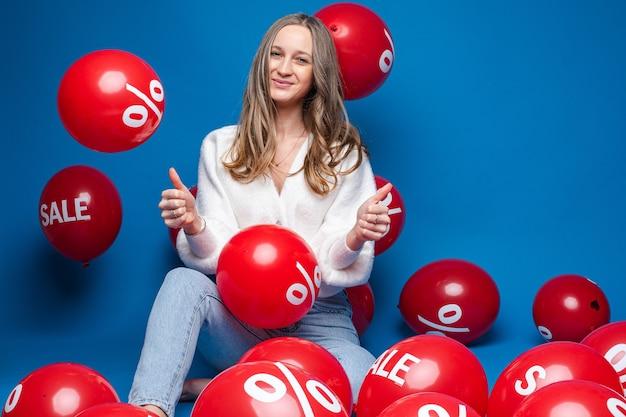 Blanke vrouw met aantrekkelijk uiterlijk zit met ballonnen met procent print en glimlacht, foto op blauw