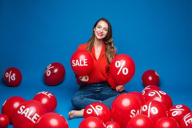 Blanke vrouw met aantrekkelijk uiterlijk zit met baloons met procent print, afbeelding op blauw