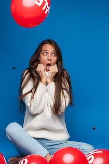 Blanke vrouw met aantrekkelijk uiterlijk zit met baloons met procent print is in shock, foto op blauw