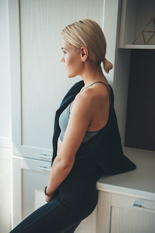 Blanke vrouw met blond haar, gekleed in sportkleding thuis poseren