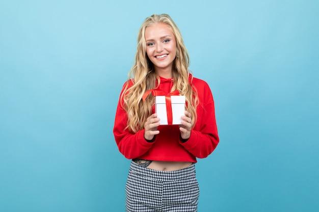 Blanke vrouw met blond haar in rood shirt houdt witte doos met cadeau en glimlacht, portret geïsoleerd op blauw