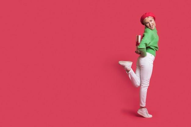 Blanke vrouw met blond haar poseert op een rode studiomuur met vrije ruimte terwijl ze een cadeau vasthoudt