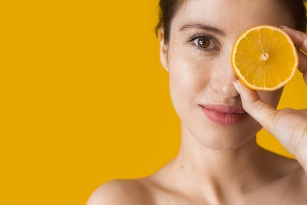 Blanke vrouw met blote schouders poseren met een sinaasappel die haar oog bedekt op een gele muur met vrije ruimte
