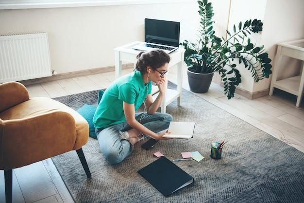 Blanke vrouw met bril studeren op de vloer uit een boek en luisteren naar muziek via oortelefoons