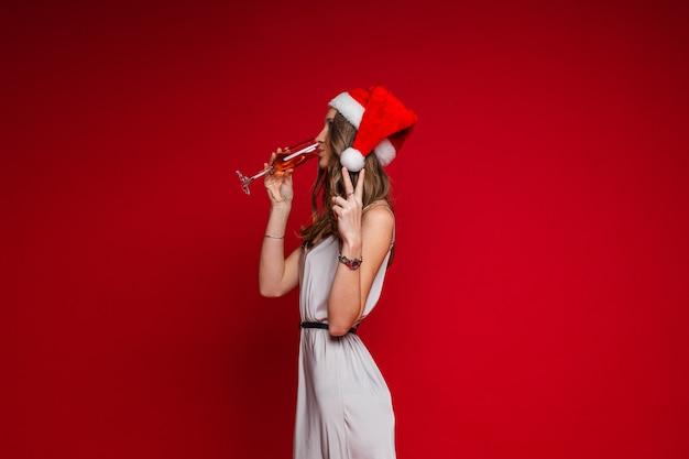 Blanke vrouw met een aantrekkelijk uiterlijk houdt een glas witte wijn vast en drinkt het, foto op rood