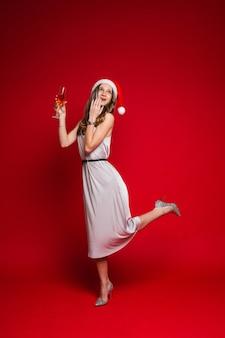 Blanke vrouw met een aantrekkelijk uiterlijk houdt een glas witte wijn vast, foto op rood