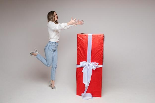 Blanke vrouw met een aantrekkelijk uiterlijk verheugt zich over een groot cadeau voor st. valentijnsdag en springt er dichtbij, foto op wit