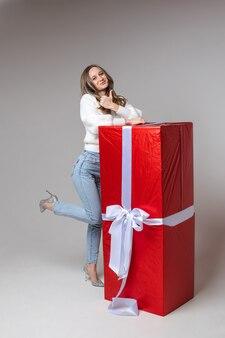 Blanke vrouw met een aantrekkelijk uiterlijk verheugt zich over een groot cadeau voor st. valentijnsdag, foto op wit