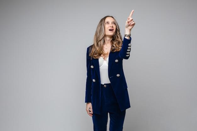 Blanke vrouw met een aantrekkelijk uiterlijk wijst iets met haar vinger omhoog, foto op grijs