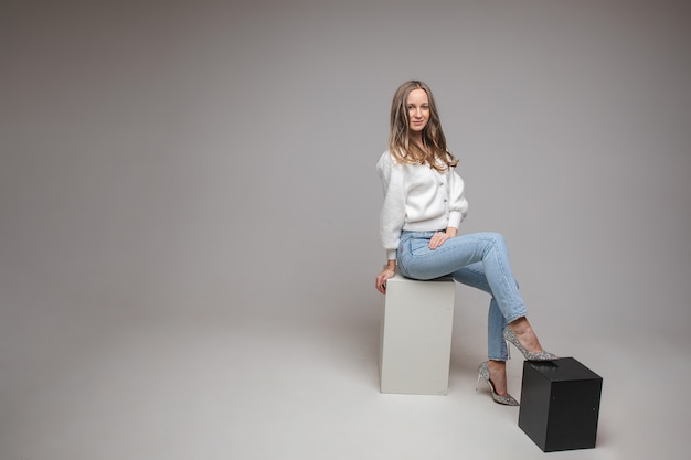 Blanke vrouw met een aantrekkelijk uiterlijk zit op een witte kubus, foto op wit