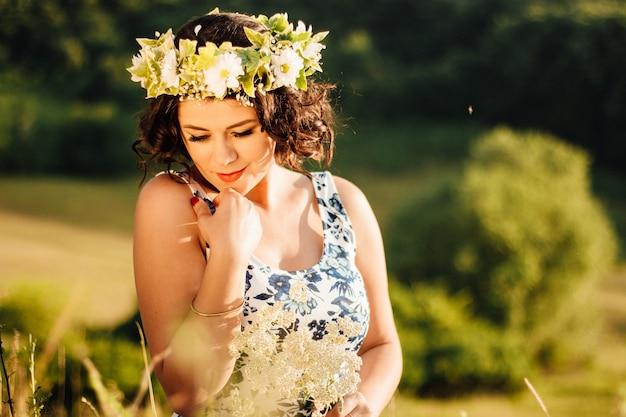 Blanke vrouw met een krans met bloemen die bloemen verzamelt in het veld