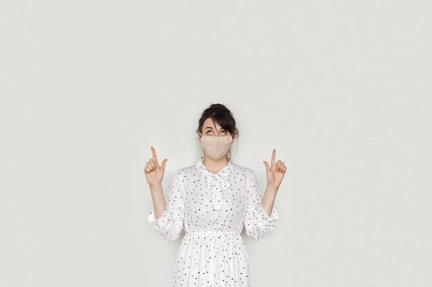 Blanke vrouw met een medisch masker wijst naar de vrije ruimte van de witte studiomuur terwijl ze poseert in een jurk
