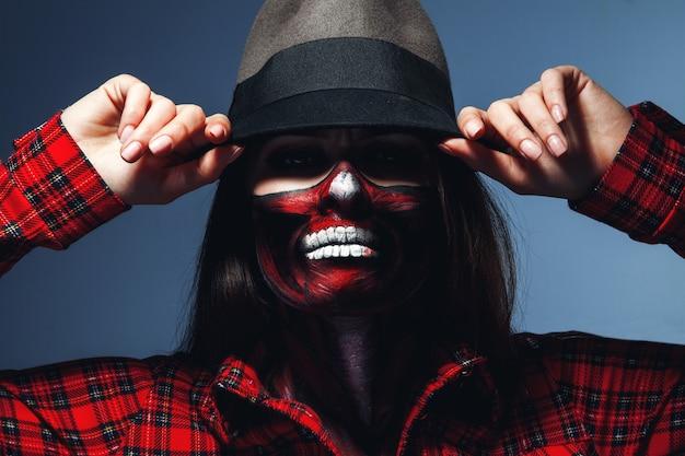 Blanke vrouw met enge halloween-gezichtskunst die camera in studio bekijkt