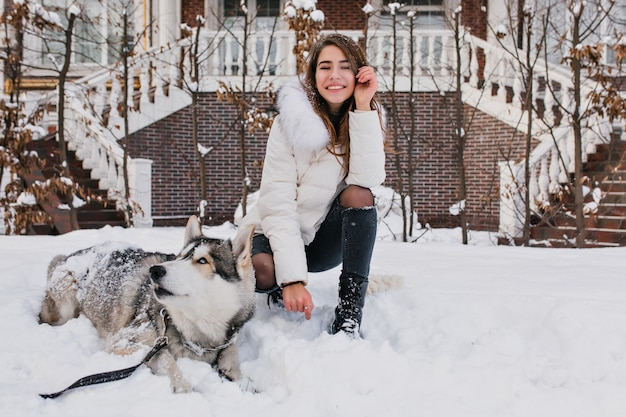 Blanke vrouw met geweldige glimlach poseren met haar hond tijdens winterwandeling in de tuin. buitenfoto van vrolijke dame draagt gescheurde spijkerbroek zittend in de sneeuw met luie husky.