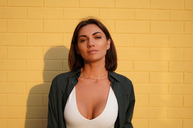Blanke vrouw met grote borsten die shirt draagt bij zonsondergang op gele bakstenen muur buiten positief